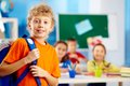 Schoolboy in school portrait of cute with backpack looking at camera with his classmates on background Royalty Free Stock Photo