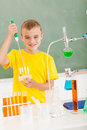 Schoolboy science class smiling primary pouring liquid in tubes in Royalty Free Stock Images