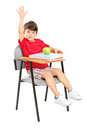 A schoolboy seated in a chair raising his hand Royalty Free Stock Photos