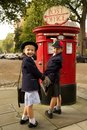 Schoolboy and sister smiling while posting letter Stock Photography