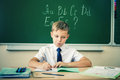 Schoolboy sits at a desk at school classroom Royalty Free Stock Photo