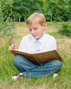 Schoolboy sitting in the park and writing in a notebook boy writes outdoors Stock Photo