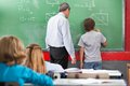 Schoolboy solving mathematics rear view of on board with teacher in classroom Royalty Free Stock Photography