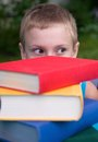 Schoolboy and stack of books Stock Images