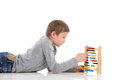 Schoolboy using an abacus lying on the floor and a colorful waist up studio shot isolated on white Stock Photography