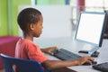 Schoolboy using computer in classroom