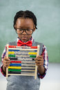 Schoolboy using a maths abacus in classroom