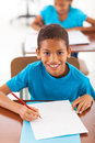 Schoolboy writing classwork cheerful african in classroom Royalty Free Stock Image
