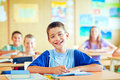 Schoolboy writing a cute sitting in his classroom with his classmates Royalty Free Stock Photo