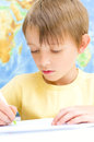 Schoolboy writing in his workbook using a pen in front of world map Stock Photography