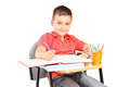 Schoolboy writing in a notebook seated on school desk isolated on white background Stock Photo