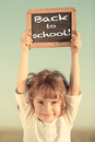 Schoolchild holding small blackboard happy smiling with text back to school against sky background Royalty Free Stock Photo
