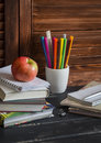 Schoolchild and student studies accessories. Books, notebooks, notepads, colored pencils, pens, rulers and a fresh red apple. Home Royalty Free Stock Photo