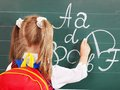 Schoolchild writting on blackboard Royalty Free Stock Photos