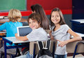 Schoolchildren with digital tablet sitting in portrait of little at desk classroom Royalty Free Stock Photography