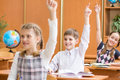 Schoolchildren with hands up at lesson in classroom school children raised Royalty Free Stock Photography