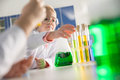 Schoolchildren in lab coats making experiment with test tubes Royalty Free Stock Photo