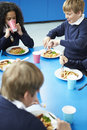 Schoolchildren sitting at table eating cooked lunch Royalty Free Stock Images