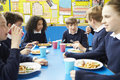 Schoolchildren Sitting At Table Eating Cooked Lunch Royalty Free Stock Photo