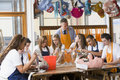 Schoolchildren and teacher sitting around a table Stock Images