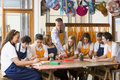 Schoolchildren and teacher sitting around a table Stock Photos