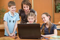 Schoolchildren and teacher using notebook at lesson laptop Royalty Free Stock Photo