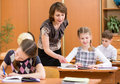 Schoolchildren work at lesson teacher controlling learning process school kids Stock Photography