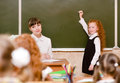 Schoolgirl answers questions of teachers near a school board Royalty Free Stock Photo