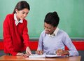 Schoolgirl asking question to female teacher at little desk in classroom Stock Photo