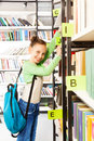 Schoolgirl with blue bag searching books Royalty Free Stock Photo