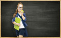 Schoolgirl with book apple and blackboard school girl child on black board background elementary education concept Stock Photo
