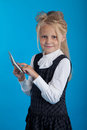 Schoolgirl with a calculator considers on the on blue background Stock Images