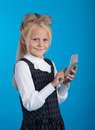Schoolgirl with a calculator considers on the on blue background Stock Image