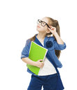 Schoolgirl child in glasses with books looking up. Royalty Free Stock Photo
