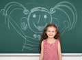 Schoolgirl child in red striped dress drawing happy man on green chalkboard background, summer school vacation concept Royalty Free Stock Photo