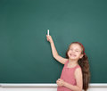 Schoolgirl child in red striped dress point and drawing on green chalkboard background, summer school vacation concept Royalty Free Stock Photo
