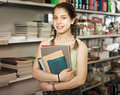 Schoolgirl choosing colored copybooks in store