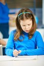 Schoolgirl concentrating writing notes exercise book class Royalty Free Stock Photos