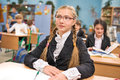 Schoolgirl cute wearing glasses swating in the classroom Royalty Free Stock Image
