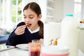 Schoolgirl With Digital Tablet And Mobile Eating Toast Royalty Free Stock Photos