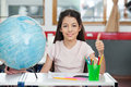 Schoolgirl gesturing thumbs up at desk portrait of cute while sitting with globe and organizer in classroom Royalty Free Stock Images