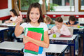 Schoolgirl gesturing thumbs up while holding books portrait of little with classmates studying in background Royalty Free Stock Photography