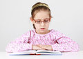 Schoolgirl with glasses reading book Royalty Free Stock Photo
