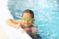 Schoolgirl with goggles in swimming pool Royalty Free Stock Photography