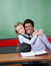 Schoolgirl hugging professor at desk portrait of happy female in classroom Royalty Free Stock Images