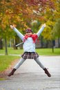 Schoolgirl jumping portrait of happy in casual in park Royalty Free Stock Images