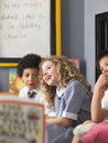 Schoolgirl laughing with boys in classroom cheerful elementary sitting Royalty Free Stock Photos