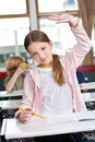 Schoolgirl raising hand at desk in classroom portrait of cute little while standing Stock Image