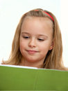 Schoolgirl reading a book enthusiastically Royalty Free Stock Images