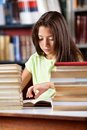 Schoolgirl reading book with stack of books at little while sitting table in library Royalty Free Stock Images